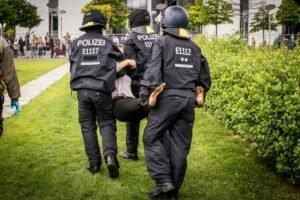 Drei Polizisten tragen einen Festgenommen fort