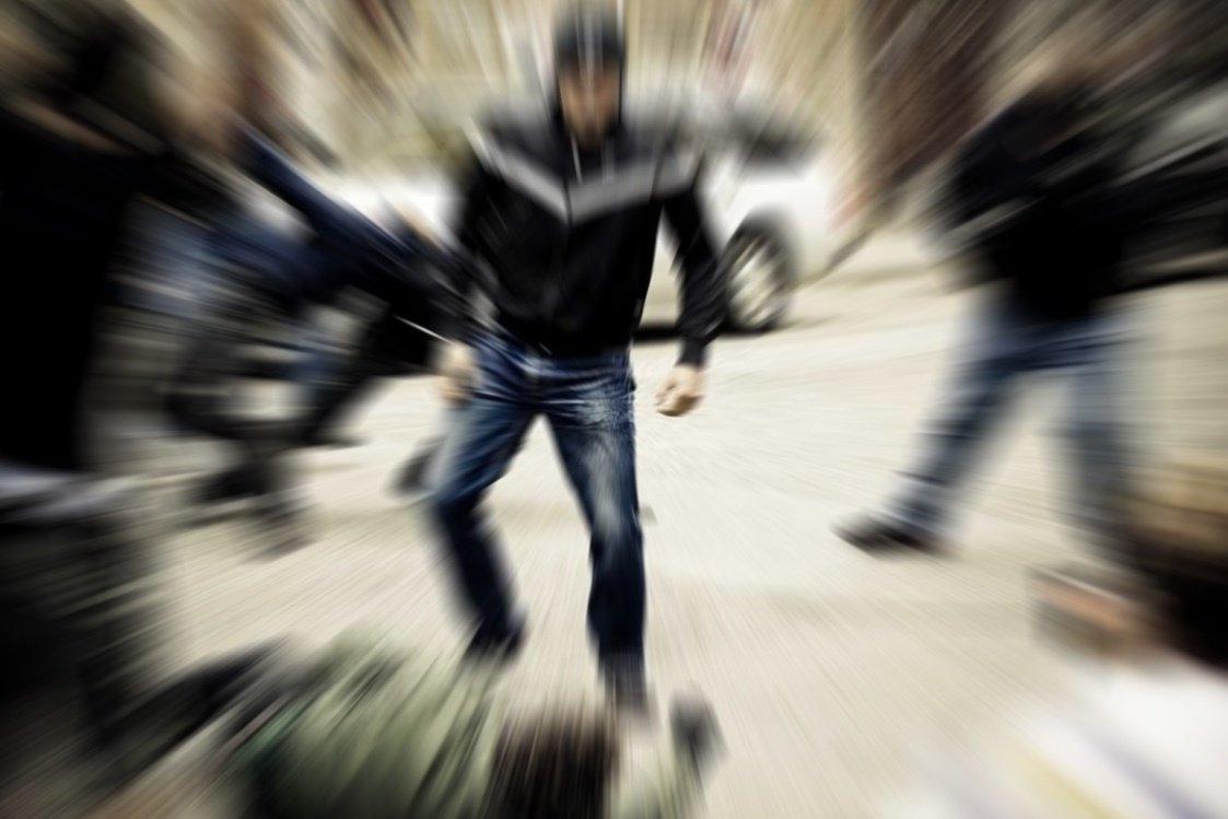 Ein Mann tritt auf einen am Boden liegenden Mann ein.